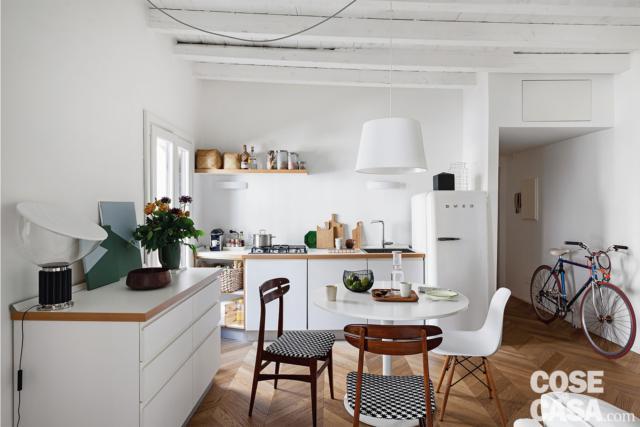mini appartement de deux pièces, coin cuisine, table à manger ronde, chaises, buffet, lampe suspendue blanche, parquet