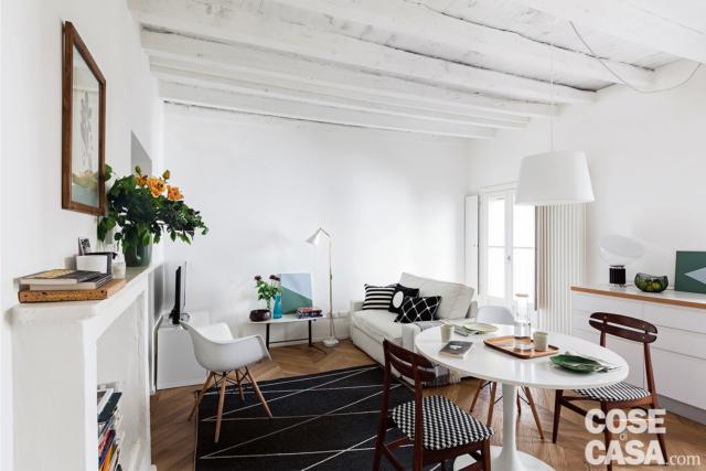 mini appartement de deux pièces, salon, salle à manger, canapé blanc, fausse cheminée, poutres apparentes blanches