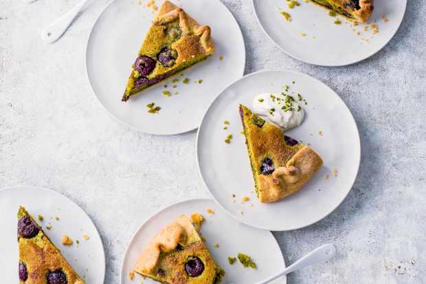 Bakewell Tarte aux cerises et galette à la pistache coupées en triangles et servies sur des assiettes blanches rondes sur une table blanche rustique