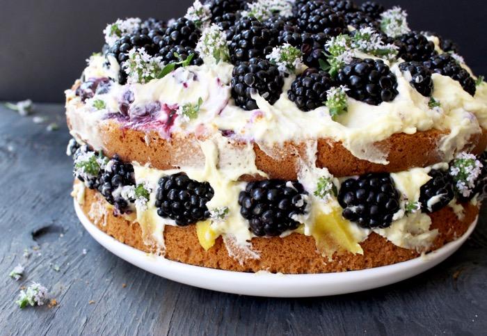 Gâteau à l'huile d'olive et au citron avec garniture de mascarpone au citron et au curd, garnie de mûres fraîches et de fleurs de thym