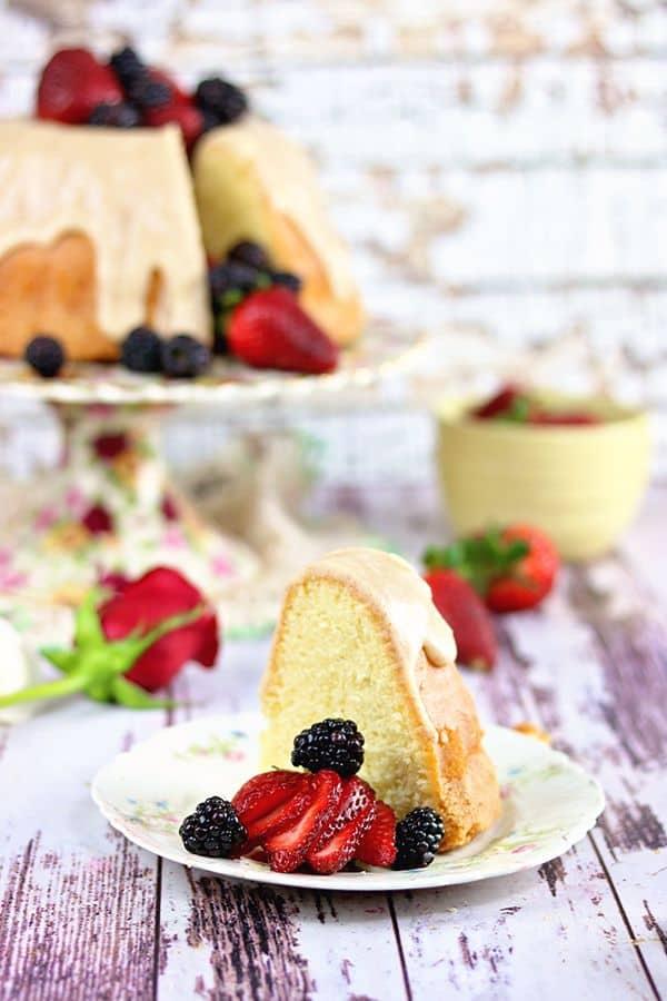 Une tranche de gâteau garnie de baies au premier plan avec l'assiette à gâteau en arrière-plan