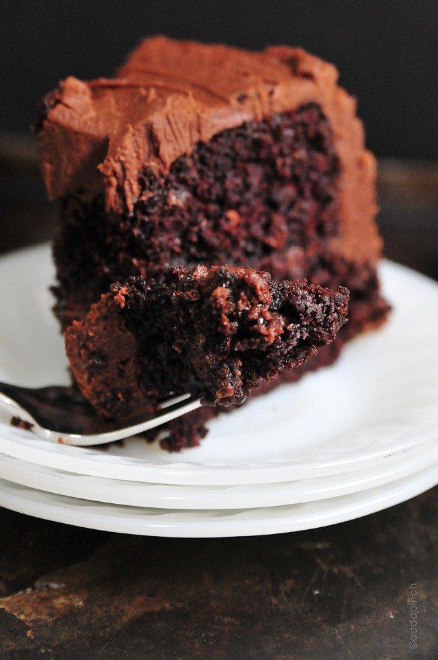 Fourchette tenant une bouchée de gâteau avec glaçage sur des assiettes à dessert blanches