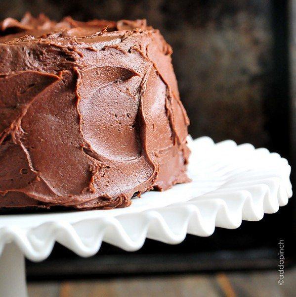 Photographie d'un gâteau avec du glaçage au beurre tourbillonné sur une assiette à gâteau blanche.