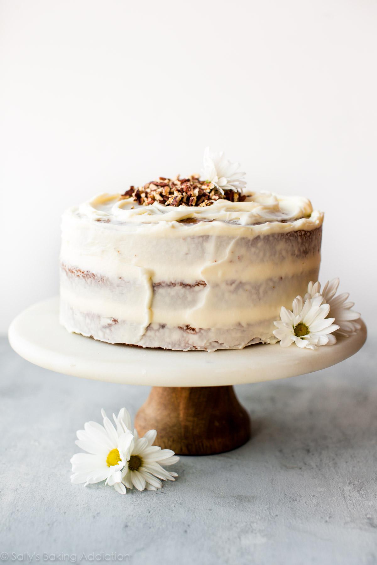 Gâteau aux carottes avec glaçage au fromage à la crème sur un support à gâteaux en marbre et bois