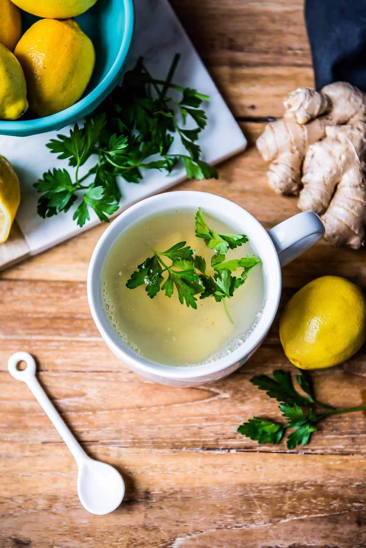 photo aérienne de la meilleure recette de thé détox, avec des ingrédients de thé nettoyants comme le citron, le gingembre et le persil