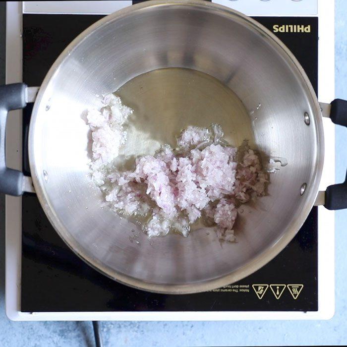 oignons finement hachés ajoutés à l'huile chaude dans un kadai