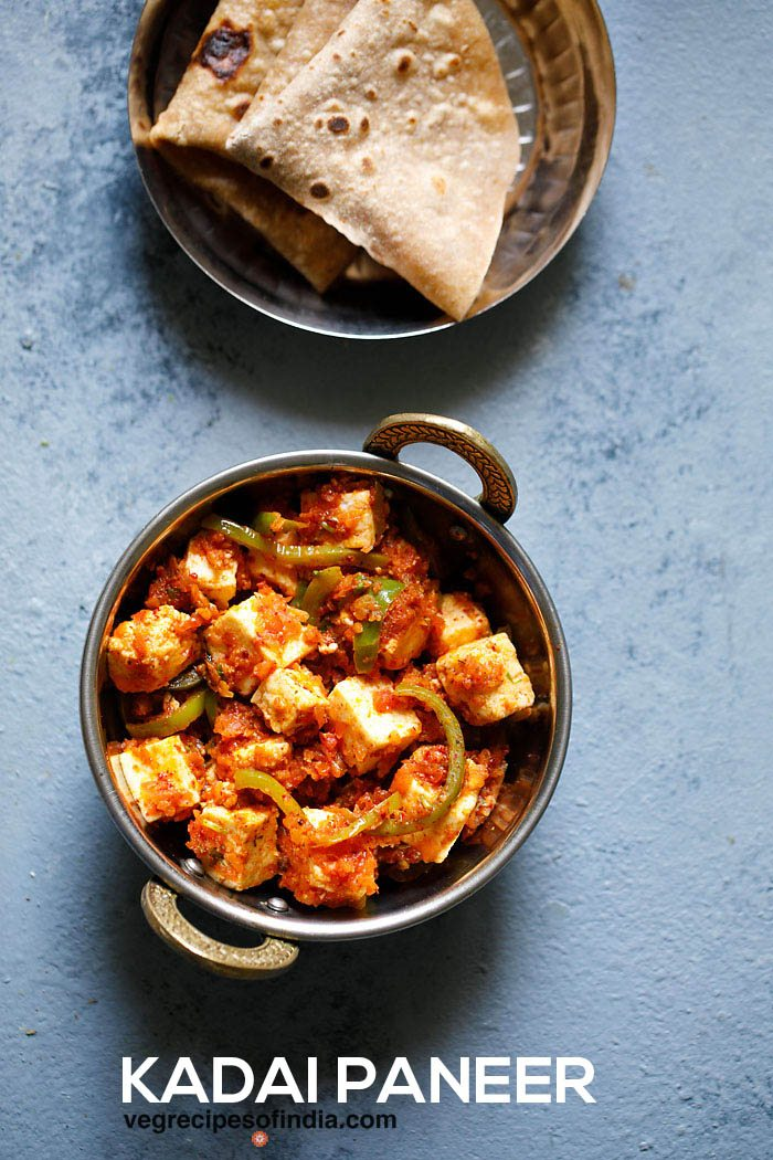 kadai paneer dans un petit kadai (wok indien) sur une planche bleu clair