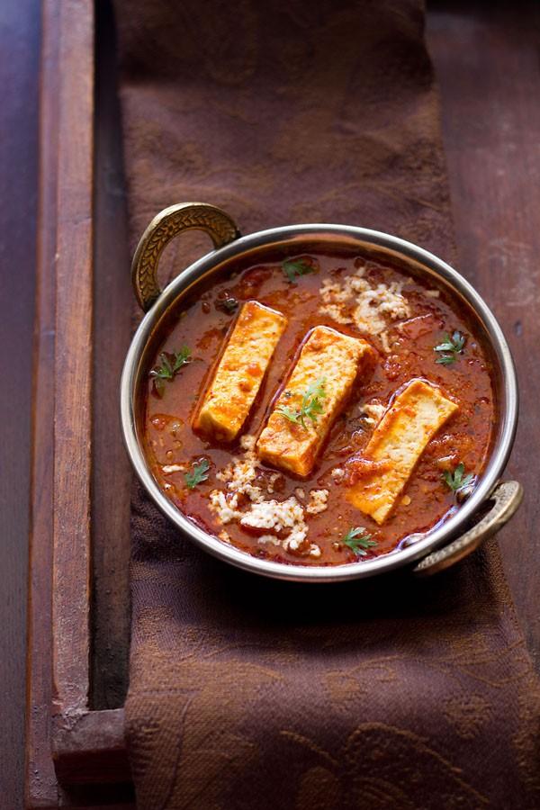 sauce recette kadai paneer dans un petit kadai en cuivre garni de brins de coriandre et de paneer râpé